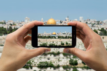 tourist holds up camera phone at the jerusalem