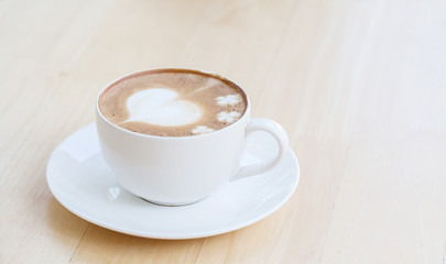 heart symbol on latte coffee cup on table