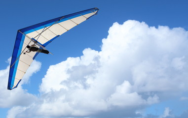 Hang Glider – Hang Glider flying through the sky white puffy clouds