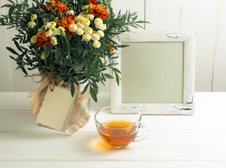 Tagetes flower bouquet with photo frame and cup of tea