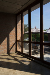 Large windows with light and shadow on brick wall