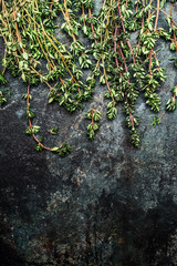Fresh thyme twigs on rustic background, top view, border