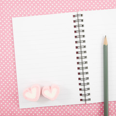 The lovely pink heart marshmallows and pencil on small white note book with pink cotton fabric.