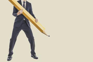 大きな鉛筆を持っているスーツのビジネスマン,全身