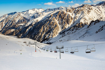 Winter mountains panorama with ski slopes and ski lifts. Skiers going down the slope under ski lift.