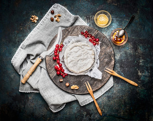 Delicious ripe camembert cheese on wooden cutting board with berries and sauce on rustic background, top view. Traditional milk dairy product