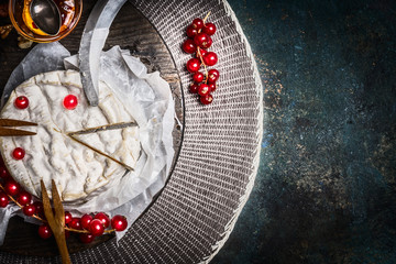 Camembert cheese plate with red currant berries and sauce on rustic background, top view, place for text. Traditional milk dairy product