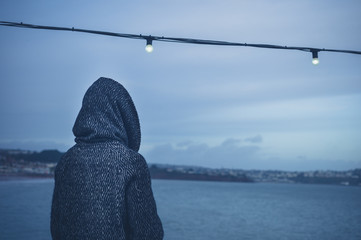 Person in hood by fairy light at sea