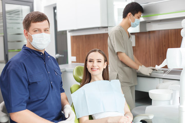 Handsome dental doctor in process of treating his patient