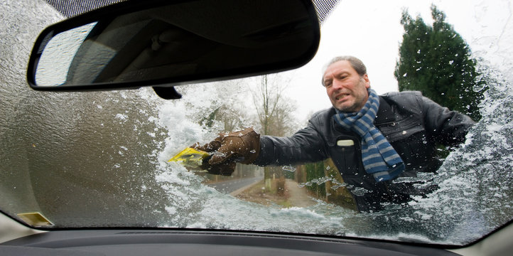 A man is scraping the ice from the windscreen of his car