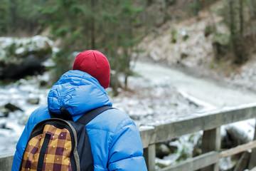 Back side of walking man hiking outdoors in winter Tatra Mountains on wooden bridge