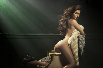Beautiful and sexy girl with fur on a vintage armchair and posing.