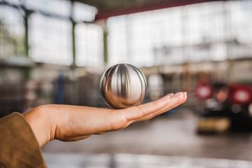 Metallkugel auf Hand balancieren