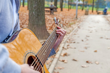 Spoed Fotobehang Oceanië Young man playing acoustic guitar close up outdoors in autumn park