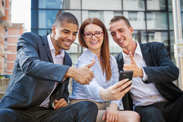 Group of business people taking selfie and looking at mobile phone. Shallow depth of field.