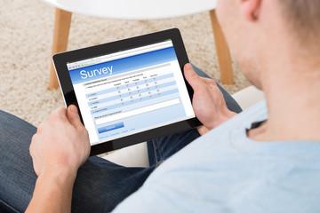 Man Filling Survey Form Online On Digital Tablet At Home