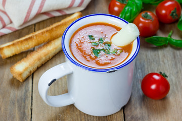 Homemade tomato basil soup in the mug, served with mozzarella cheese stick and croutons