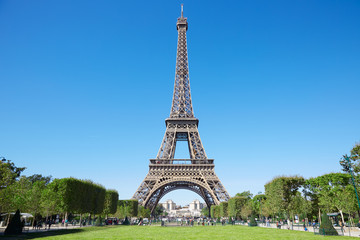 Photo sur Toile Tour Eiffel Eiffel tower, sunny summer day with blue sky and green Field of Mars
