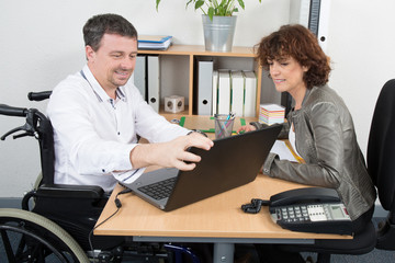 Smiling spastic businessman disabled interviewing candidate woman in an office