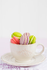 Colorful tiny macaroons in vintage coffee cup