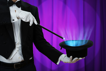 Magician Holding Wand Over Illuminated Hat