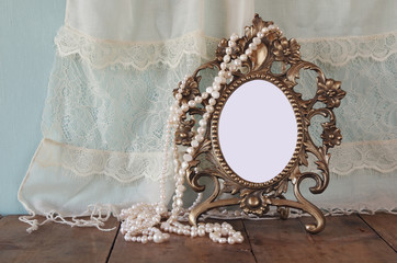 Antique blank victorian style frame, and white pearls on wooden table. retro filtered and toned image. template, ready to put photography