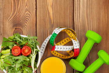 Dumbells, tape measure and healthy food over wooden table