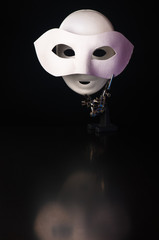Mask in the mask, iron alligator clip stand with two white masks on a black background