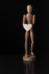 Wooden mannequin with a heart on a black background