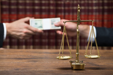 Justice Scale On Table With Judge Taking Bribe From Client
