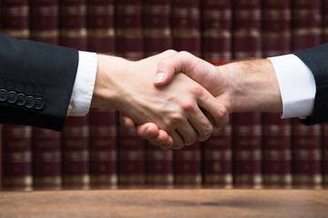 Judge And Client Shaking Hands Against Books
