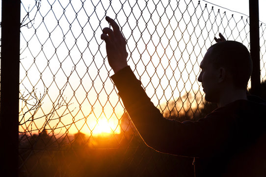 silhouette of a man behind the fence on the background of sunset