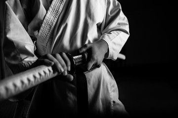 Deurstickers Vechtsport Close up of young martial arts fighter with katana siting in seiza position, black and white.