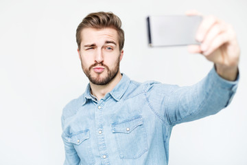 Handsome Man takes a Selfie with Smartphone