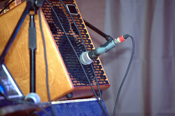 Sound amplifying equipment: microphone and midsize sound speaker system in brown wooden cabinet on concert stage