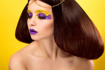 The avantaged portrait girl with an unusual make up , Portrait on a yellow background, custom volume hairstyle metal ornament in the form of fragments,fashionable toning