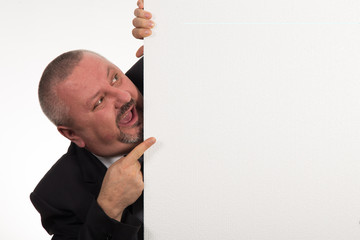 Businessman pointing to whiteboard he is hiding behind