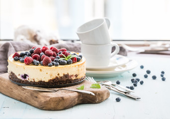 Cheesecake with fresh raspberries and blueberries on a wooden serving board, plates, cups, kitchen napkin, silverware over blue background, window at the backdrop.