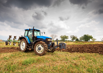 Wall Mural - Blue tractor and dramatic sky.