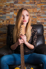 Attractive young girl in blue jeans and black lace shirt sitting in chair and holding guitar on brick background