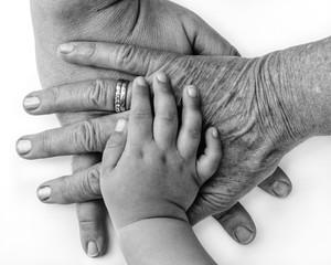 Hände dreier Generationen übereinander in schwarz weiß