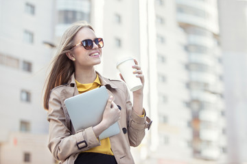 Business morning / Beautiful young businesswoman with a disposable coffee cup, drinking coffee, and holding tablet in her hands against urban city background.