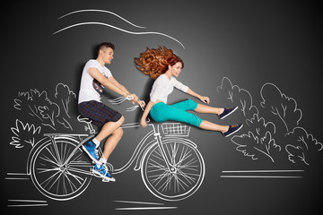 Quick as the wind / Happy valentines love story concept of a romantic couple against chalk drawings background. Male riding his girlfriend in a front bicycle basket.