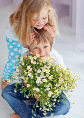 Happy kids with camomile bouquet at home