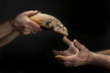 Mano di donna dona pagnotta di pane a un povero senzatetto. Concetto di povertà , emarginazione , fame nel mondo