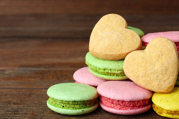 Spoed Foto op Canvas Macarons delicious macaroons and cookies in the shape of a heart on a brown wooden table