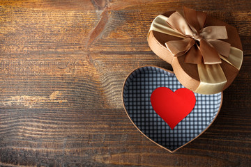a paper heart in a box in the shape of heart with bow on wooden table