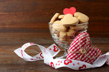 cookies in the shape of a heart in the ice cream bowls on a wooden table next to a decorative heart with ribbon