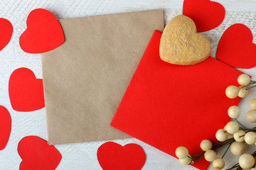 cookies in the shape of a heart and a paper heart on wooden table