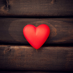 Red heart on the dark boards